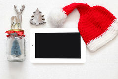 On line christmas holiday shopping concept. Santa claus red hat next to tablet device Stock Images