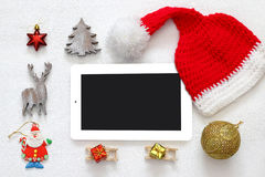 On line christmas holiday shopping concept. Santa claus red hat next to tablet device Royalty Free Stock Photography