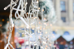 Line of Christmas lights in a Christmas market during the day. Line of white Christmas lights in a Christmas market during the day Royalty Free Stock Images