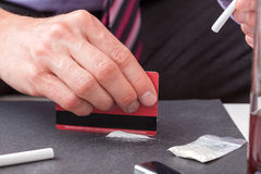 Line of cocaine. A hand making a line of cocaine with a credit card Stock Image