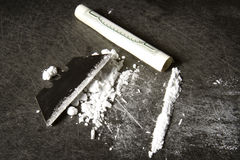 Line of Cocaine. Powdered cocaine prepared in a line with razor blade and rolled up hundred dollar bill Royalty Free Stock Photos
