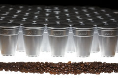 Line of coffee beans in front of plastic cups Royalty Free Stock Images