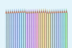 Line of colored pencils on light blue background Stock Images