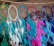 Line of colorful dream catchers with feathers and beads hanging in a market. Line of pink, blue, purple, green and white dream catchers with feathers, silver royalty free stock photography