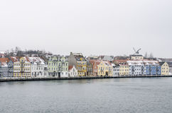 Line of colorful houses next to the water with a wind mill in a background. Sea water landscape with a horizon filled by shiny bright houses during a grey day Stock Photo
