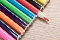 Line of colorful pencil crayons on wood. With a single red one arrange facing in the opposite direction Stock Image
