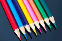 Line of colorful wooden pencils on black background Royalty Free Stock Images