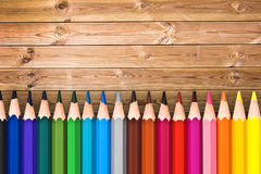 Line of colorful wooden pencils on wood planks Royalty Free Stock Images