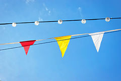 Line of colourful festival flags and lamps against blue sky Stock Photography