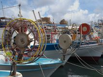 A line of colourful traditional fishing boats moored in paphos harhour in cyprus with blue summer sky and clouds. A line of colourful traditional line fishing Stock Images