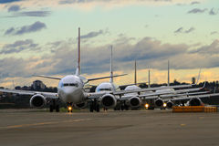 Line of commercial airliners on runway. Line of commercial jet airliners waiting on busy runway Royalty Free Stock Photography