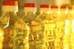 Line or conveyor for food production of sunflower oil. Bottles with vegetable oil close-up against the background of factory equipment Royalty Free Stock Image