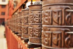 Line of copper praying drums. Line of vintage copper praying drums with sanskrit symbols Royalty Free Stock Photos