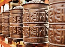 Line of copper praying drums. Line of vintage copper praying drums with sanskrit symbols Royalty Free Stock Photography