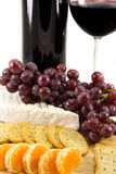 Line of crackers and clementins. Picture of some grapes brie and some clementins with a bottle of red wine in the background stock images