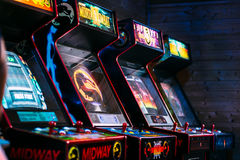 Line of cult action old arcade video games from late 90`s era. In a dark gaming room Royalty Free Stock Images