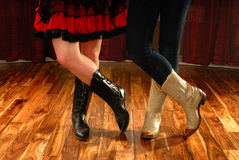 Line Dance Legs in Cowboy Boots. Female Legs in Cowboy Boots in a Line Dance Step on hardwood floor stock photo