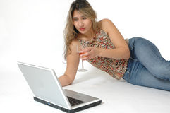 On Line Dating. Beautiful latino woman surfing the internet chatting and dating on line. Woman relaxing on the floor and drinking a glass of wine as she shops on royalty free stock photography