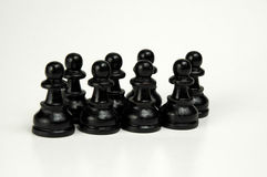 Line of Defense. Group of black pawns, isolated Stock Photo