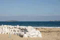 Line of defense. In late summer on the beach building barricades of sandbags Stock Photography