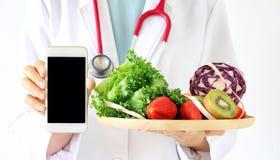 On-line-Diätberater, Doktor, der intelligentes Telefon, frische Frucht hält stockfoto