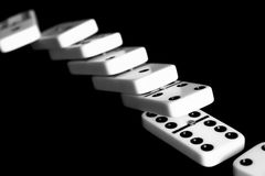 Line of dominoes in black background and selective focus. Fallen dominoes, concept of chain reaction, defeat, game, etc Royalty Free Stock Images