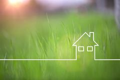 Sunny green eco house icon on grass background. With a line drawn green eco house icon on sunny blurred grass copy space background. Selective focus used Stock Images