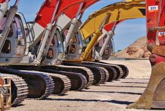 Line of earth movers. Parked in the desert showing details of continuous tracks and hydraulics stock images