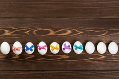 Line of Easter eggs with colorful bows are on the wooden background Royalty Free Stock Photography