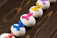 Line of easter eggs with colorful bows are on the wooden background. Diagonal view Stock Image
