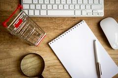 On-line-Einkaufen - hölzerner Schreibtisch oben mit wenigem Einkaufsdiagramm stockfotos