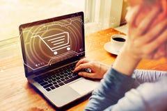 On-line-Einkaufsthema mit dem Mann, der einen Laptop verwendet lizenzfreie stockbilder