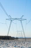 Line of electric pylons on winter field Royalty Free Stock Photo