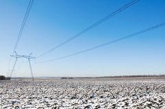 Line of electric pylons on winter field Stock Photos