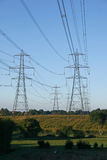 Line of Electricity Pylons across countryside Stock Photo