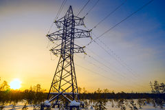 Line of electricity transmission in the winter at sunset. Royalty Free Stock Photography