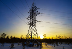 Line of electricity transmission in  winter at sunset. Royalty Free Stock Images