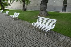 Line of empty white benches in the park Royalty Free Stock Image