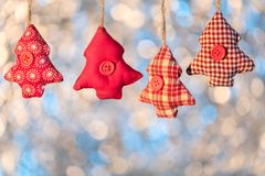 Line of fabric red Christmas trees on bokeh background, shallow Royalty Free Stock Photography