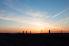 Line of Fence Posts Against Golden Sunset Stock Photos