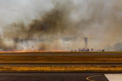Line of flame approaches equipment Airport brush fire El Salvadore. SAN SALVADORE, EL SALVADOR - MARCH 3, 2013: Flames and black smoke close San Salvador Stock Images