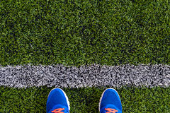 Line on the floor. White stripes and man shoe on the grass floor. Line on soccer field Royalty Free Stock Photography