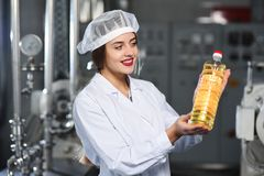 Line of food production of refined sunflower oil. Girl worker at a factory on a conveyor background with bottles of vegetable oil Stock Images