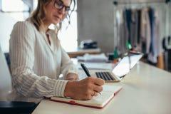 On-line-Geschäftseigentümer, der an ihrem Schreibtisch arbeitet lizenzfreies stockbild