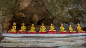 In-line golden Buddha statues in Khao Luang Cave - Phetchaburi, Thailand. PHETCHABURI, THAILAND - SEPTEMBER 17: In-line golden Buddha statues on September 17 stock photos