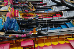 A line of gondolas. Gondolas tied up in a line on the Grand Canal in Venice. The gondolas are all done out with many different colour interiors. They are done in Stock Photography