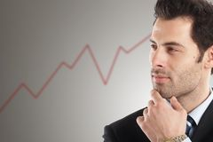 Line Graph. Handsome Businessman looking at line graph in background Royalty Free Stock Photo