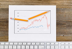 Line graph reflecting market conditions on a rustic wooden desk Stock Photos