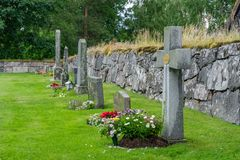 Line with grave stones with colorful flowers and green grass royalty free stock photography