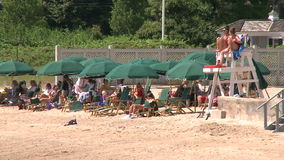 A line of green beach umbrellas next to a lifeguard stand stock video